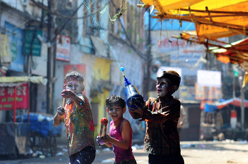 . Indian children covered in colored powder spray colored water during Holi festival celebrations in Allahabad on March 17, 2014. Holi, the popular Hindu spring festival of colors is observed in India at the end of the winter season on the last full moon of the lunar month. AFP PHOTO/SANJAY Kanojia/AFP/Getty Images