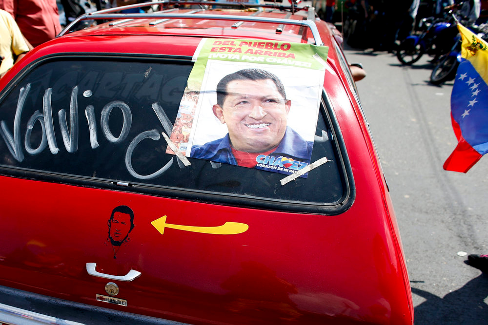 Description of . A car with a picture and poster of Venezuela's President Hugo Chavez and the word
