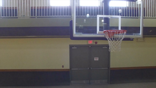Aerial Zoom Out From Basketball Goal In Gym