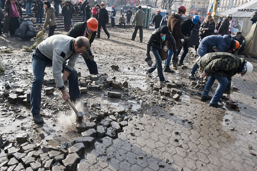 . Anti-government protesters dig up cobblestones to use them as rocks against riot police on Kiev\'s Independence square on February 19, 2014.  AFP PHOTO / PIERO  QUARANTA/AFP/Getty Images