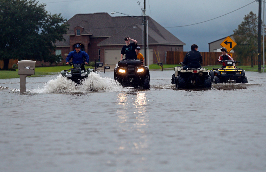 . Kids ride an ATV in a street flooded by Tropical Storm Harvey, in the Clearfield Farm subdivision in Lake Charles, La., Tuesday, Aug. 29, 2017. (AP Photo/Gerald Herbert)