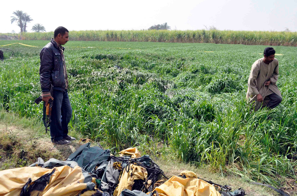 . A security officer and a rescue official examine the wreckage of a hot air balloon that crashed in Luxor February 26, 2013.  A hot air balloon crashed near the Egyptian town of Luxor at dawn on Tuesday after a mid-air gas explosion, killing 19 Asian and European tourists, a local industry official and the state news agency said. REUTERS/Stringer