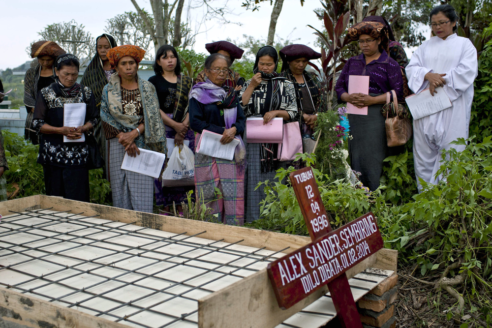 . Relatives pray during the burial of a victim that was killed after being hit by pyroclastic smoke from the eruption of Mount Sinabung on February 02, 2014 in Suka village, Karo District, North Sumatra, Indonesia. The number of displaced people has increased to around 30,000 in Western Indonesia as Mount Sinabung continues to spew ash and smoke after a series of several eruptions since September. At least 15 people have been killed in a eruption of Mount Sinabung, as residents returned to their local homes after they were told by authorities that activity was decreasing. (Photo by Ulet Ifansasti/Getty Images)