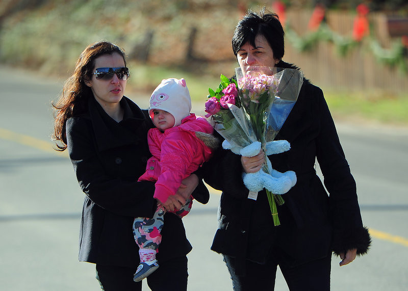 . Residents arrive to pay tribute to the victims of an elementary school shooting in Newtown, Connecticut, on December 15, 2012. A young gunman slaughtered 20 small children and six teachers on December 14 after walking into a school in an idyllic Connecticut town wielding at least two sophisticated firearms.      EMMANUEL DUNAND/AFP/Getty Images