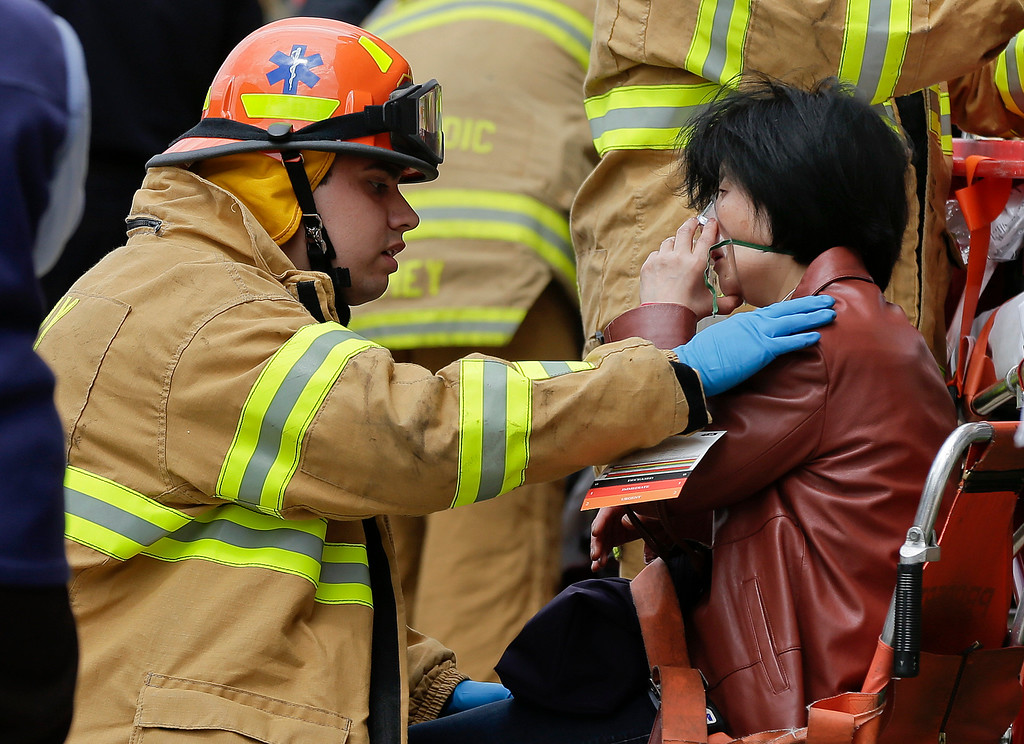 . A New York City fire department EMT assists a woman who was evacuated from a subway train after it derailed in the Queens borough of New York, Friday, May 2, 2014.  The express F train was bound for Manhattan and Brooklyn when it derailed at 10:40 a.m. about 1,200 feet (365 meters) south of the 65th Street station, according to the Metropolitan Transportation Authority. Dozens of firefighters and paramedics with stretchers converged on Broadway and 60th Street, where passengers calmly left the tunnel through the sidewalk opening. A few were treated on stretchers. (AP Photo/Julie Jacobson)