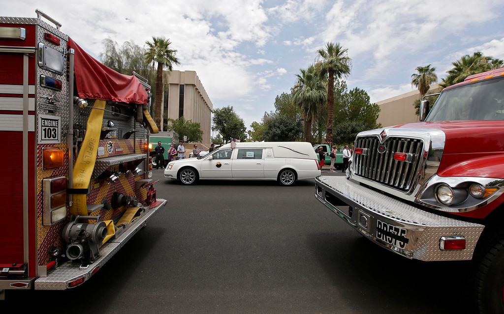 . A procession of 19 hearses for the 19 firefighters killed in a wildfire a week ago drives through Phoenix, Sunday, July 7, 2013 The elite crew of firefighters were overtaken by the out-of-control blaze as they tried to protect themselves from the flames under fire-resistant shields. (AP Photo/Chris Carlson)