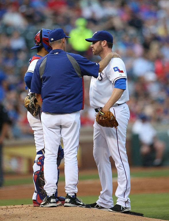 . Robinson Chirinos #61 looks on as pitching coach Mike Maddux #31 pitching coach talks with Colby Lewis #48 of the Texas Rangers after allowing two men on base in the second inning against the Colorado Rockies at Globe Life Park in Arlington on May 7, 2014 in Arlington, Texas.  (Photo by Rick Yeatts/Getty Images)