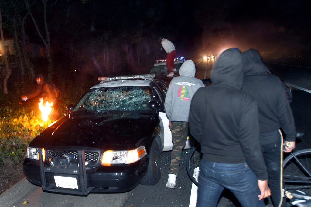 . A CHP squad car is vandalized on a Highway 24 offramp in Oakland, Calif., Sunday evening, Dec. 7, 2014, during a second consecutive night of civil disobedience in Berkeley and Oakland over the killings of two unarmed black men by police in Ferguson, Mo., and New York. (Karl Mondon/Bay Area News Group)