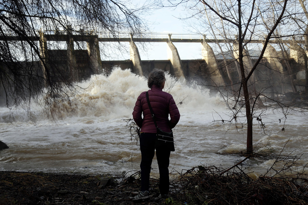 . Chris Buchanan watches the overflow at a dam on Vasona Lake after a series of storms Tuesday, Jan. 24, 2017, in Los Gatos , Calif. (AP Photo/Marcio Jose Sanchez)