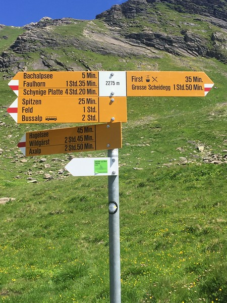 Hiking post with hiking routes and distances on a Switzerland hiking trip.