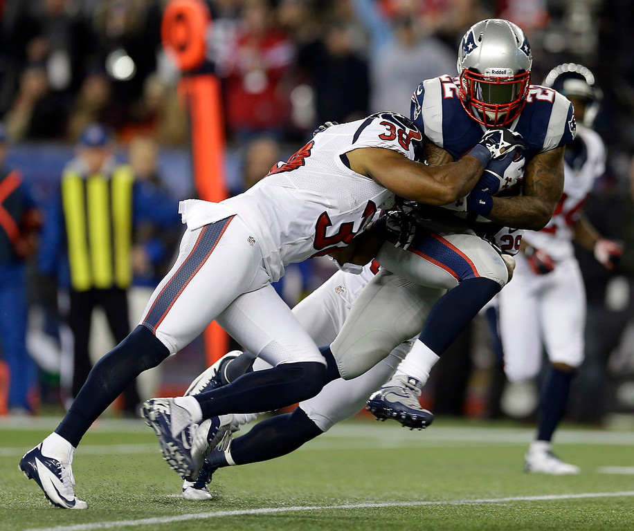 . New England Patriots running back Stevan Ridley (22) scores on an eight-yard touchdown run while being tackled by Houston Texans free safety Danieal Manning during the second half of an AFC divisional playoff NFL football game in Foxborough, Mass., Sunday, Jan. 13, 2013. (AP Photo/Elise Amendola)