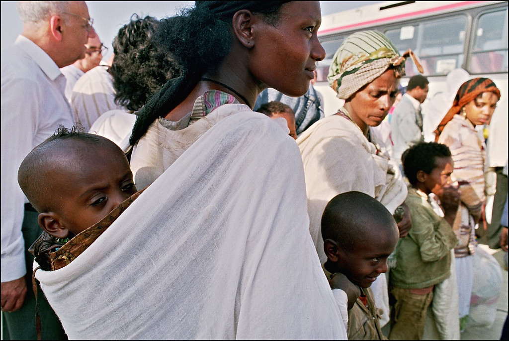 """. TEL-AVIV, ISRAEL:  Jewish Ethiopian mothers known as \""""Falashas\"""" disembark with their children from a plane from Addis Ababa 25 May 1991. \""""Falashas\"""" were evacuated from Ethiopia as part of \""""Operation Solomon\"""", the world\'s largest airlift carried out out by Israeli army. The large numbers of emigrants from Ethiopia and, primarily, from the Soviet Union, increased Israel\'s population by nearly 10 % in 3 years (between 1989-92). SVEN NACKSTRAND/AFP/Getty Images"""