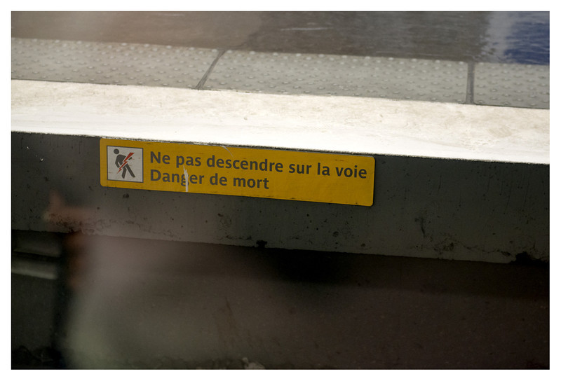 """Scary sign next to a Paris Metro track.  """"Do not step on the track - danger of death"""".  Yikes."""