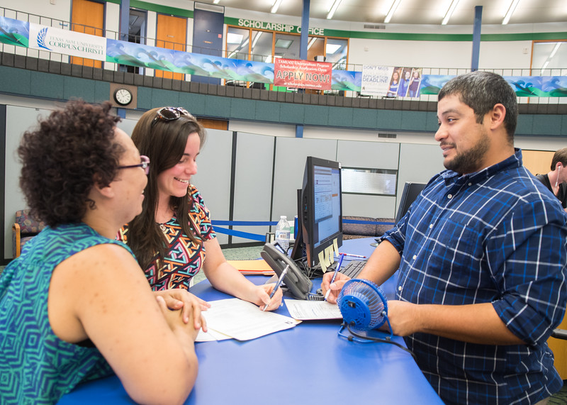 Deshawna Colvin (left) and Leslee Shauer are helped by Leo Gomez at the Registrar's Office in the Student Services Building.