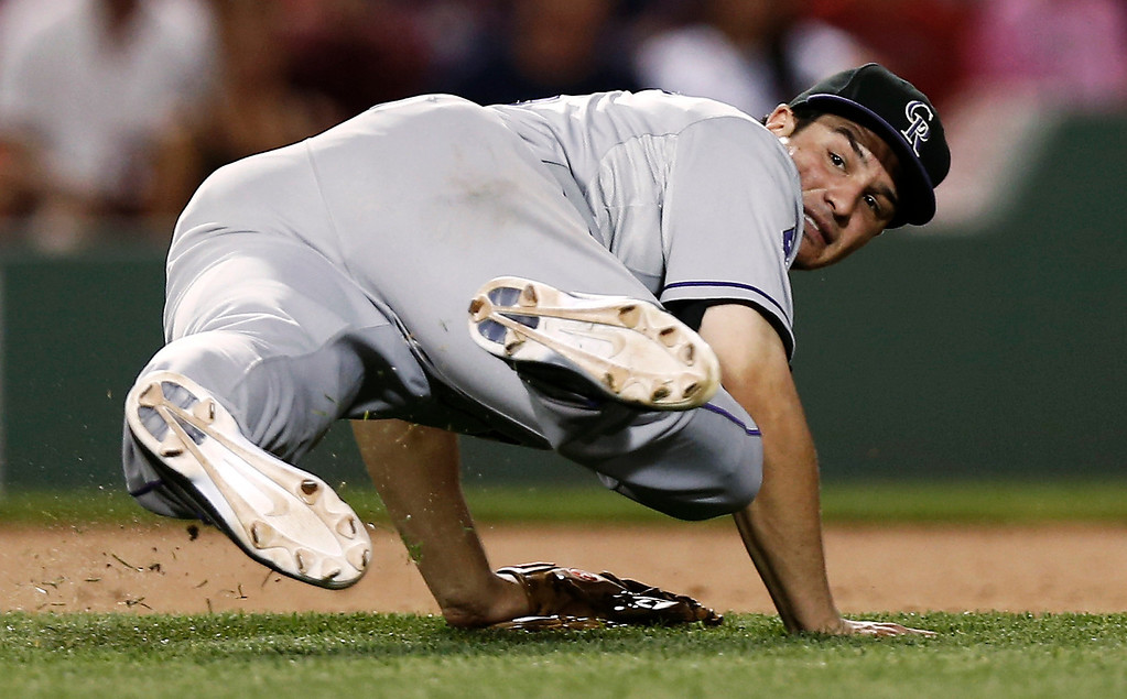 . Colorado Rockies third baseman Nolan Arenado looks back to first base after falling while trying to throw out Boston Red Sox\'s Jacoby Ellsbury on an infield hit during the seventh inning of a baseball game at Fenway Park in Boston on Tuesday, June 25, 2013. (AP Photo/Winslow Townson)