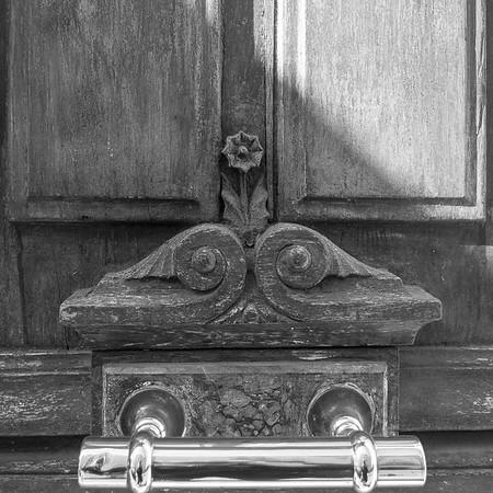 Brass door handle and ancient wood carving, Rue de Jean Beauvais, Paris