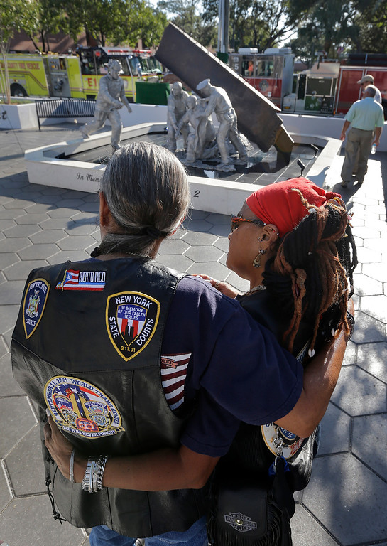 . Jorge, left, and Lisa Maldonado, of New York City, hug as they reflect at a 9/11 Fallen Heroes Memorial after it was unveiled outside the Hillsborough County Sheriff\'s Office, Thursday, Sept. 11, 2014, in Tampa, Fla. The memorial includes a beam from the World Trade Center Tower 2.  (AP Photo/Chris O\'Meara)