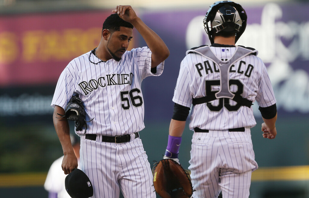 . Colorado Rockies starting pitcher Franklin Morales, left, waits to confer with catcher Jordan Pacheco after walking New York Mets\' Chris Youngin the first inning of a baseball game in Denver, Saturday, May 3, 2014. (AP Photo/David Zalubowski)