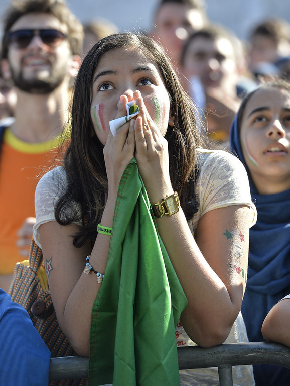 . An Italian fan reacts as she watches on a giant screen the World Cup football match Italy vs Costa Rica on June 20, 2014 on the Piazza Venezia square in Rome. (ANDREAS SOLARO/AFP/Getty Images)