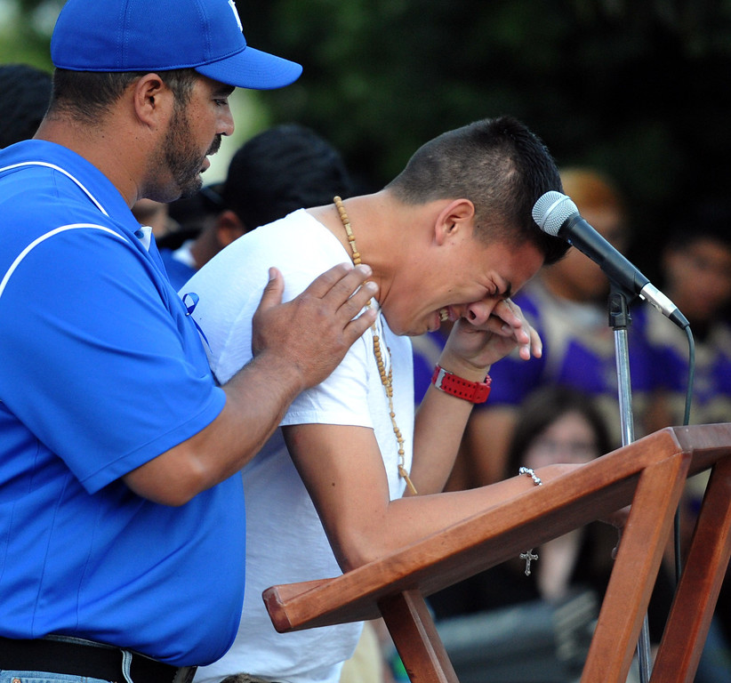 . Football coach Joel Sanchez holds up a student who was on the bus when it crashed, cries as he tells the story as family, students and members of the community gather in memory of Adrian Castro, 19, at El Monte High School Monday evening April 14, 2014. Castro was one of nine students killed in the bus crash in Orland, Calif. (Staff Photo by Keith Durflinger/San Gabriel Valley Tribune)
