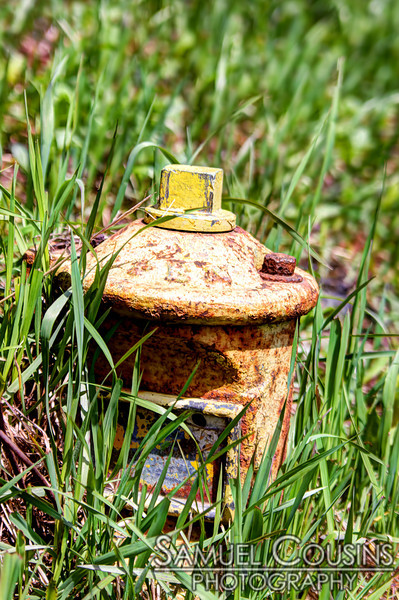 An old rusty shut-off in the grass.