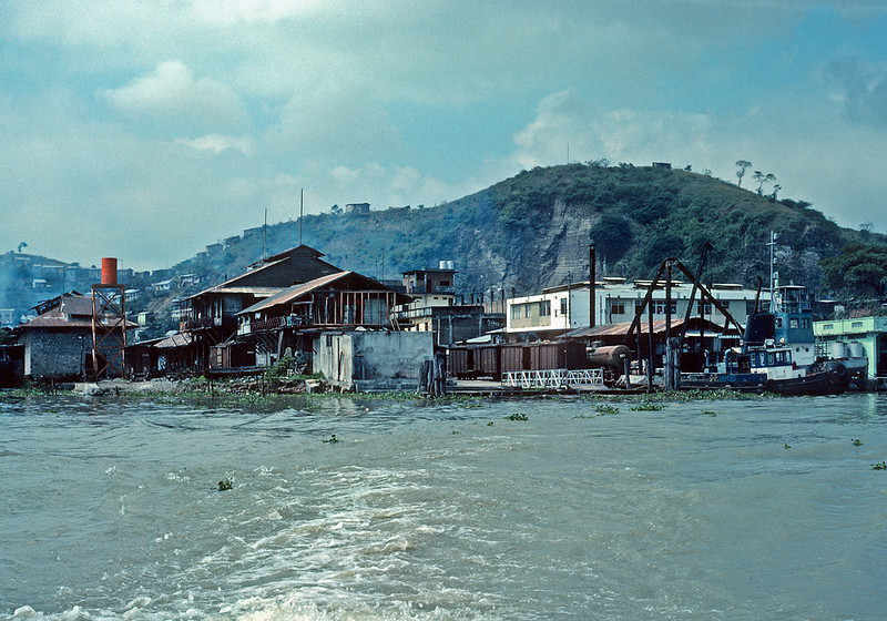 July 1976.  Crossing the river from Guayaquil to Duran.  The railroad headquarters is the group of ramshackle buildings pictured.  When I returned in 2003 this was all gone (they would say redeveloped or something).
