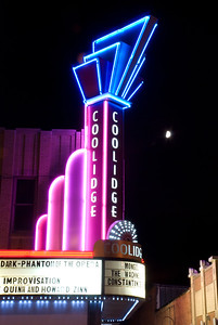 The Coolidge Corner Theater lit up at night with their art deco theater neon sign glowing and the moon in the sky. You have to love this theater