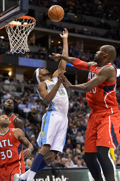 . Corey Brewer (13) of the Denver Nuggets throws up an awkward shot on Johan Petro (10) of the Atlanta Hawks March 4,  2013 at Pepsi Center. (Photo By John Leyba/The Denver Post)