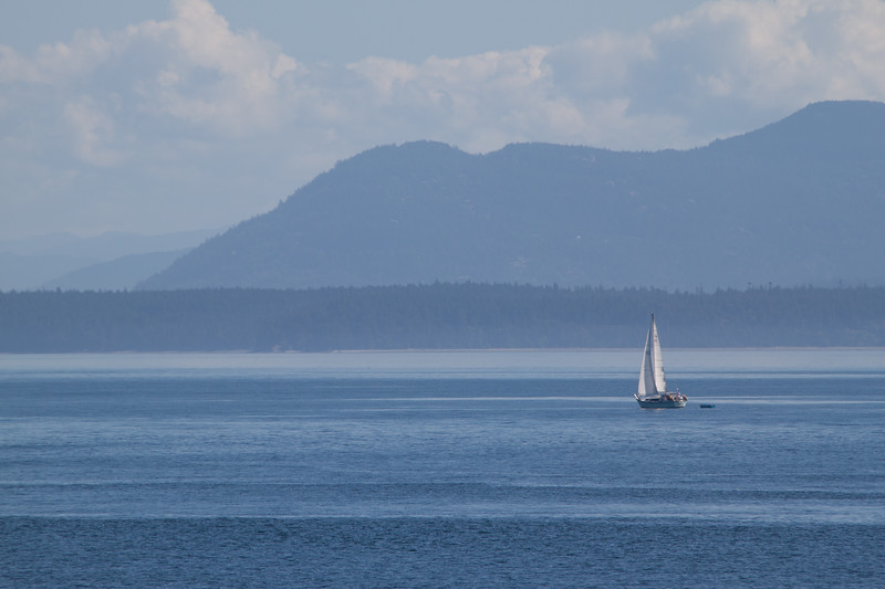 Long view of a sailboat on calm waters in