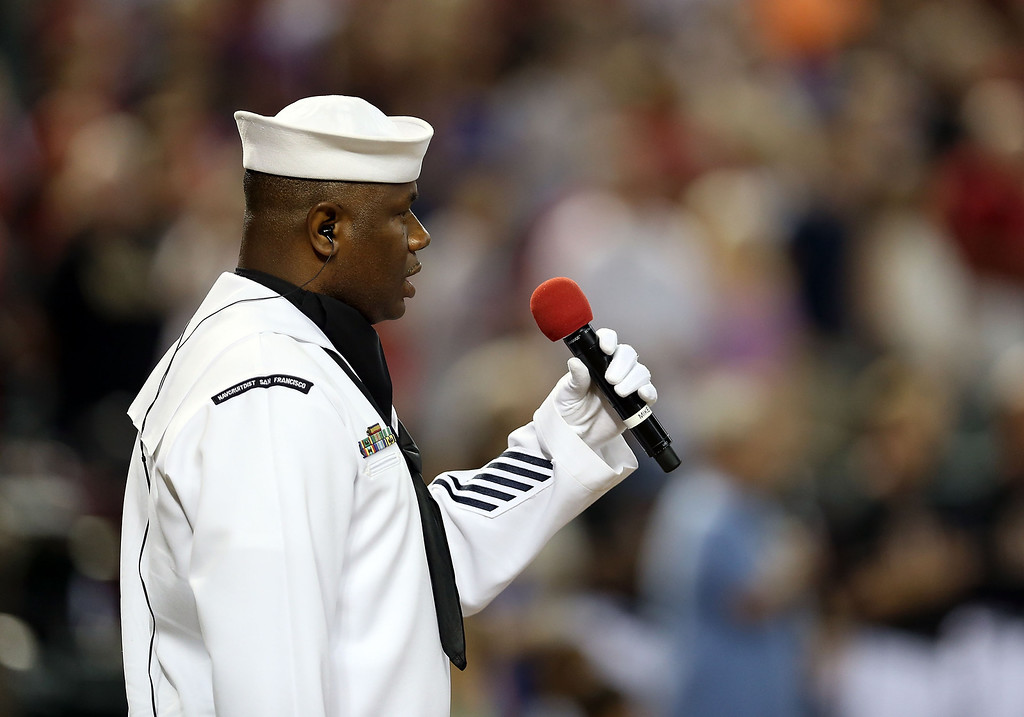 """. PHOENIX, AZ - JULY 05:  Petty Officer Steven Powell - US Navy performs the National Anthem before the MLB game against the Colorado Rockies at Chase Field on July 5, 2013 in Phoenix, Arizona. The Arizona Diamondbacks are wearing a \""""19\"""" patch in honor of the 19 Granite Mountain Interagency Hotshot Crew firefighters who died battling a fast-moving wildfire near Yarnell, AZ.  (Photo by Christian Petersen/Getty Images)"""