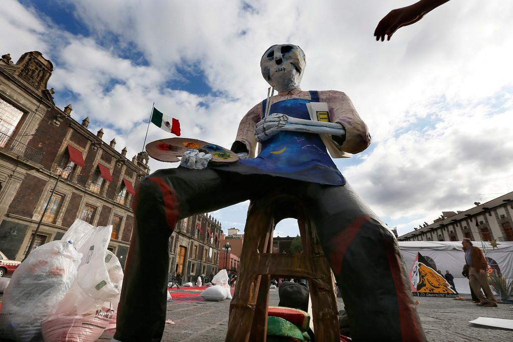 . Skeletons decorate Mexico City\'s main square, the Zocalo, as part of the Day of the Dead festivities in Mexico City, Thursday, Oct. 27, 2016. The holiday honors the dead as friends and families gather in cemeteries to decorate their loved ones\' graves and hold vigil through the night on Nov. 1 and 2. (AP Photo/Marco Ugarte)