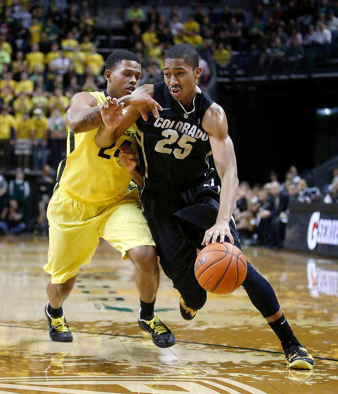 . Colorado\'s Spencer Dinwiddie (25) drives against Oregon\'s Willie Moore during the first half of an NCAA college basketball game at Matthew Knight Arena in Eugene, Ore. Thursday, Feb. 7, 2013. (AP Photo/Brian Davies)