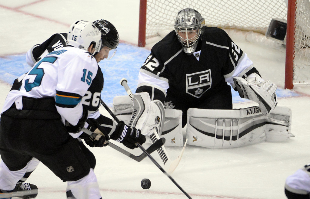 . Los Angeles Kings goalie Jonathan Quick (32) blocks a shot by San Jose Sharks left wing James Sheppard (15) as defenseman Slava Voynov (26) defends during the first period in Game 4 of an NHL hockey first-round playoff series at Staples Center in Los Angeles on Thursday, April, 24  2014.  (Keith Birmingham Pasadena Star-News)