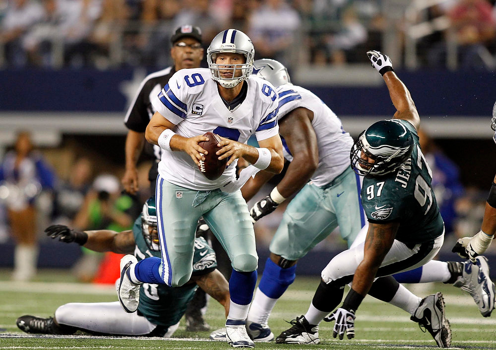 . Dallas Cowboys quarterback Tony Romo scrambles as Philadelphia Eagles defensive tackle Cullen Jenkins is unable to make the tackle in the first half of their NFL football game in Arlington, Texas December 2, 2012.  REUTERS/Mike Stone