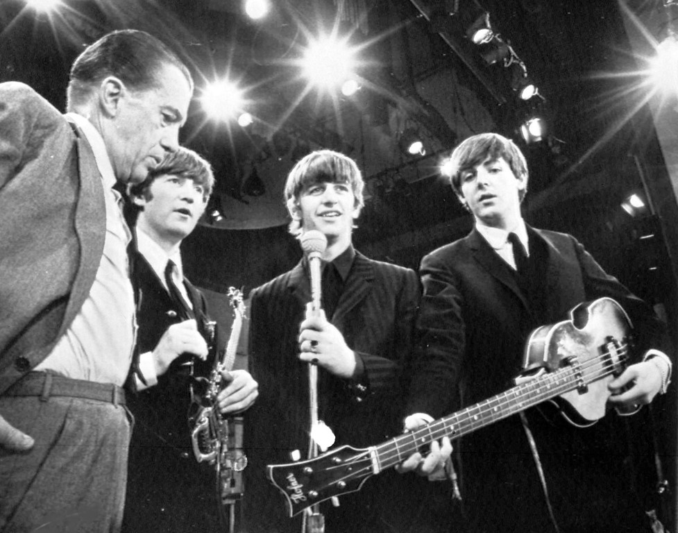 . American TV host Ed Sullivan, left, talks with three members of the British pop group The Beatles during a rehearsal for their appearance on his TV show, in New York, Feb. 8, 1964. From left, Sullivan, John Lennon, Ringo Starr and Paul McCartney. George Harrison, the fourth member of the group missed the rehearsal due to illness. (AP Photo)