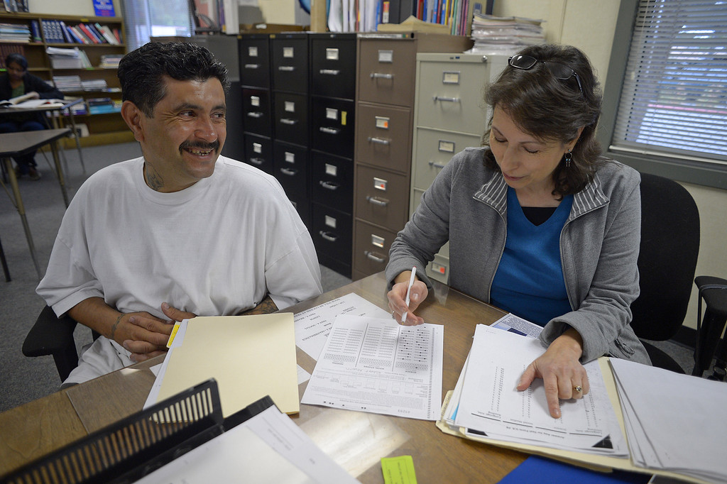 . Robert Nevotti, of Antioch, smiles as his GED teacher Betty Cusack grades his GED science practice test while attending a six week GED summer class at the Pittsburg Adult Education Center in Pittsburg, Calif. on Monday, June 24, 2013. The GED, is undergoing an overhaul in January, switching to computers, condensing from five tests to four, requiring more analysis and a deeper understanding of math. At the end of December, many students who have begun taking the five tests currently necessary to obtain the certificate are ramping up their efforts, because they\'ll have to start over if they\'re not done by Dec. 31. (Jose Carlos Fajardo/Staff)