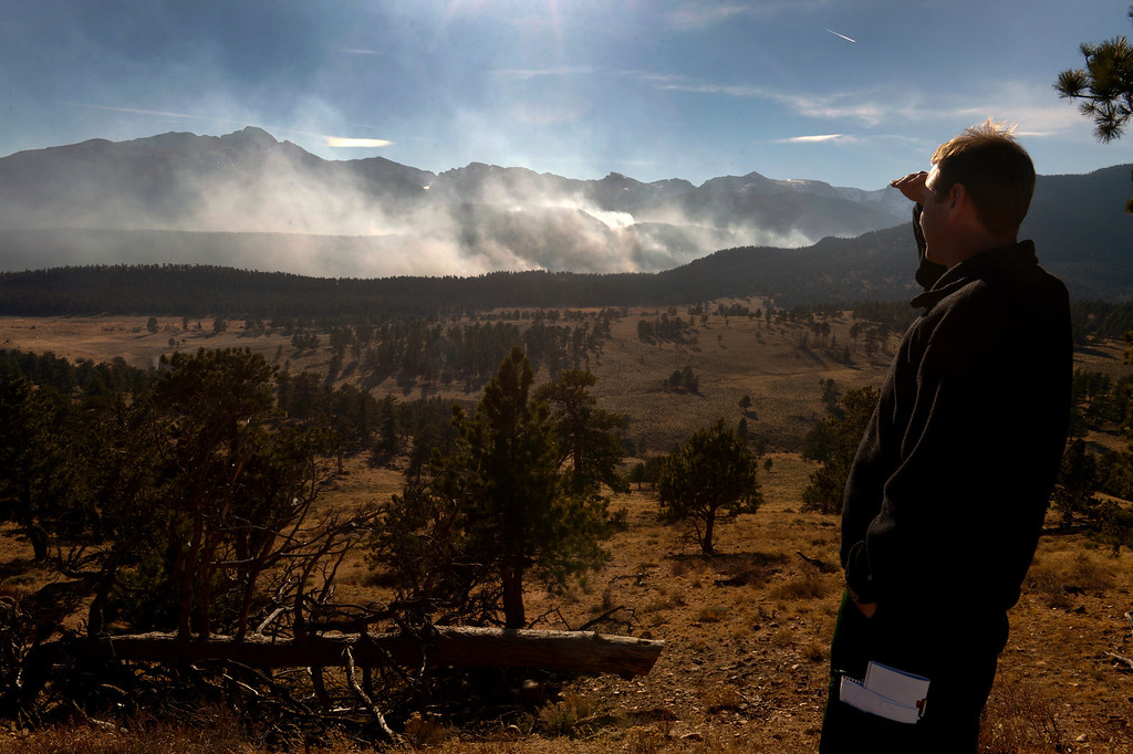 . Jake Brollier, Public Information Officer on the Fern Lake Fire, looks at the fire from the main road inside of the park. Officials are worried about winds kicking up later in the afternoon on December 2, 2012.
