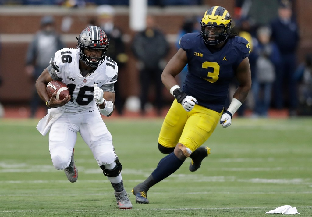 . Ohio State quarterback J.T. Barrett (16) is chased by Michigan defensive lineman Rashan Gary (3) during the first half of an NCAA college football game, Saturday, Nov. 25, 2017, in Ann Arbor, Mich. (AP Photo/Carlos Osorio)