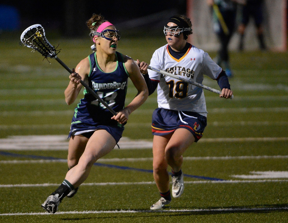 . LITTLETON, CO - MAY 8: Haley Kroll, left, ThunderRidge High School, heads down field against Bailey Dodd, Heritage/Littleton, during the second half of play at Littleton Public Schools Stadium for the first round of the 2013 Colorado Girls State Lacrosse Championships May 8, 2013. ThunderRidge won 8-5. (Photo By Andy Cross/The Denver Post)