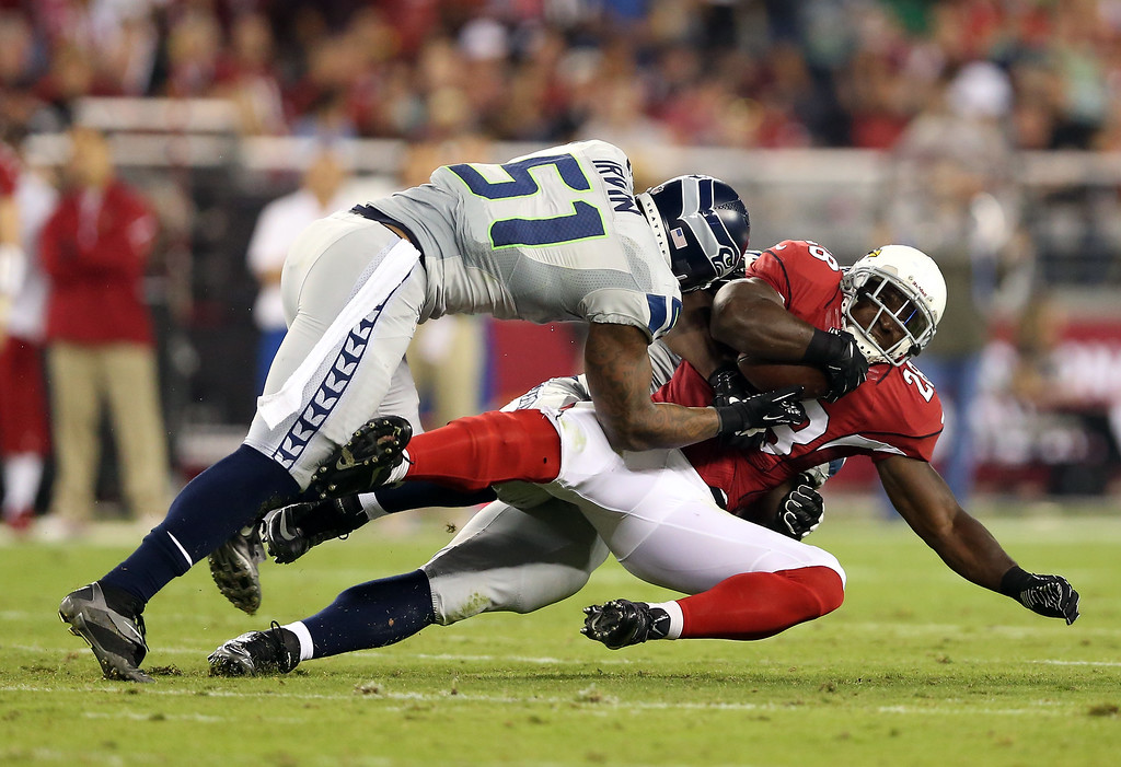 . GLENDALE, AZ - OCTOBER 17: Running back Rashard Mendenhall #28 of the Arizona Cardinals is tackled for a loss by outside linebacker Bruce Irvin #51 of the Seattle Seahawks in the second quarter during a game at the University of Phoenix Stadium on October 17, 2013 in Glendale, Arizona.  (Photo by Christian Petersen/Getty Images)