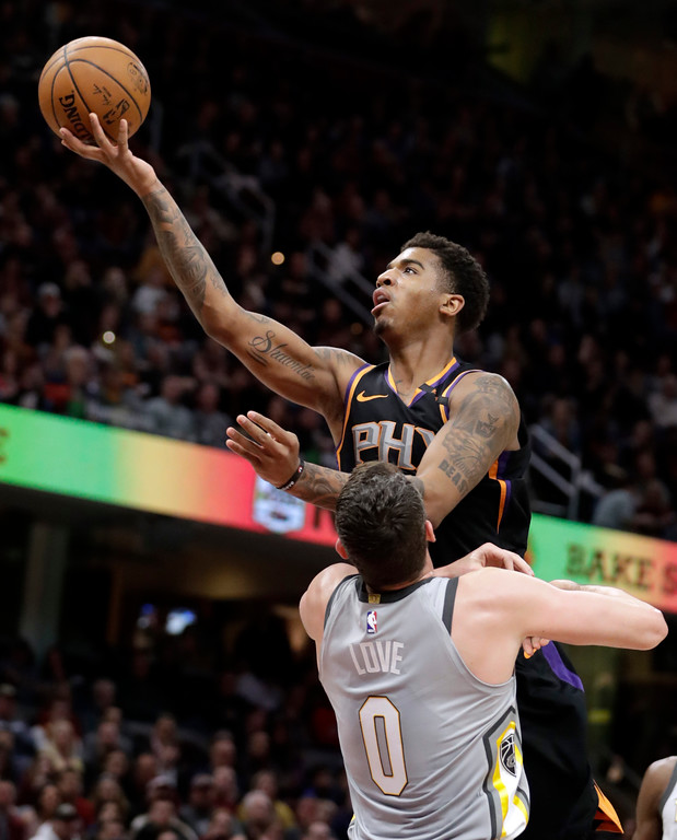 . Phoenix Suns\' Marquese Chriss shoots over Cleveland Cavaliers\' Kevin Love during the first half of an NBA basketball game Friday, March 23, 2018, in Cleveland. (AP Photo/Tony Dejak)