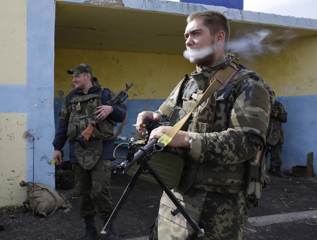 . Ukrainian soldiers smoke as they guard at a checkpoint controlled by Ukrainian forces on September 10, 2014, near the small eastern Ukrainian city of Slavyanoserbsk, in the Lugansk region. AFP PHOTO/ ANATOLII STEPANOVANATOLII STEPANOV/AFP/Getty Images