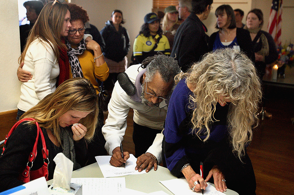 . Community members pen notes to the families of slain Santa Cruz Police detectives Loran \'Butch\' Baker and Elizabeth Butler as other mourners console each other at a vigil for the officers at the Louden Nelson Community Center Wednesday evening.  (Dan Coyro/Sentinel)