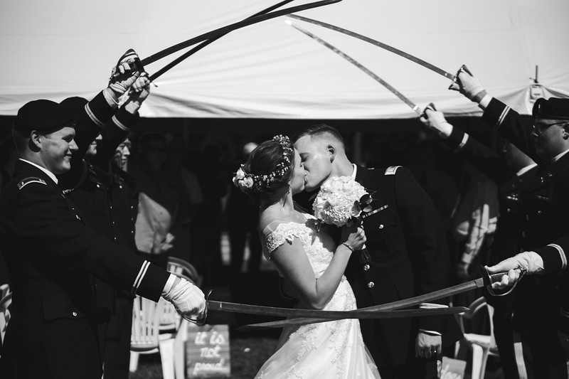 The groom dips the bride and kisses her passionately under a arch of made by the swords of Army officers.