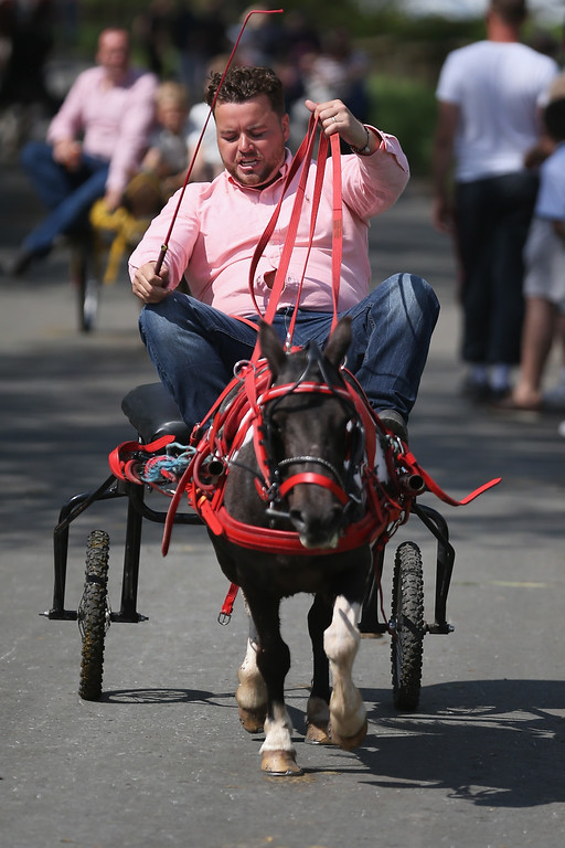 . Travellers race their horses along the \'Mad Mile\' during the Appleby Horse Fair on June 4, 2015 in Appleby, England. The Appleby Horse Fair has existed under the protection of a charter granted by James II since 1685 and is one of the key gathering points for the Romany, gypsy and traveling community. The fair is attended by about 5,000 travelers who come to buy and sell horses. The animals are washed and groomed before being ridden at high speed along the \'mad mile\' for the viewing of potential buyers.  (Photo by Christopher Furlong/Getty Images)