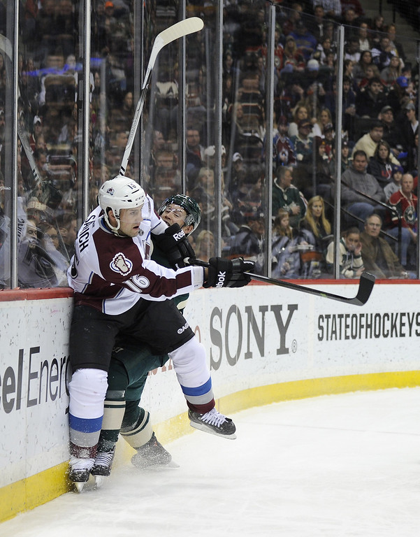 . Matt Cooke #24 of the Minnesota Wild checks Cory Sarich #16 of the Colorado Avalanche into the boards during the second period of the game on November 29, 2013 at Xcel Energy Center in St Paul, Minnesota. The Avalanche defeated the Wild 3-1. (Photo by Hannah Foslien/Getty Images)