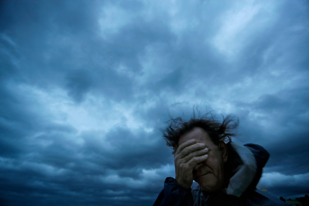 . Russ Lewis covers his eyes from a gust of wind and a blast of sand as Hurricane Florence approaches Myrtle Beach, S.C., Friday, Sept. 14, 2018. (AP Photo/David Goldman)