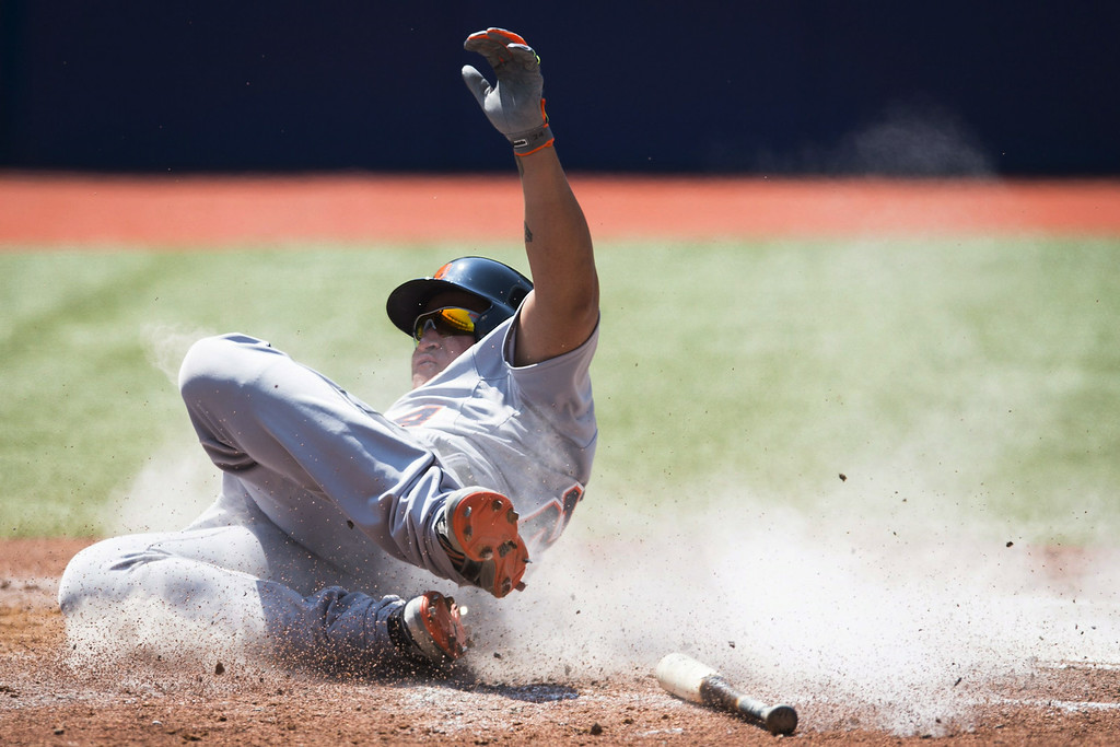 . Detroit Tigers\' Miguel Cabrera slides safely into home plate to score on Victor Martinez\'s two-RBI double in the sixth inning of of a baseball game against the Toronto Blue Jays, Saturday, Aug. 9, 2014 in Toronto. The Blue Jays defeated the Tigers 3-2. (AP Photo/The Canadian Press, Darren Calabrese)