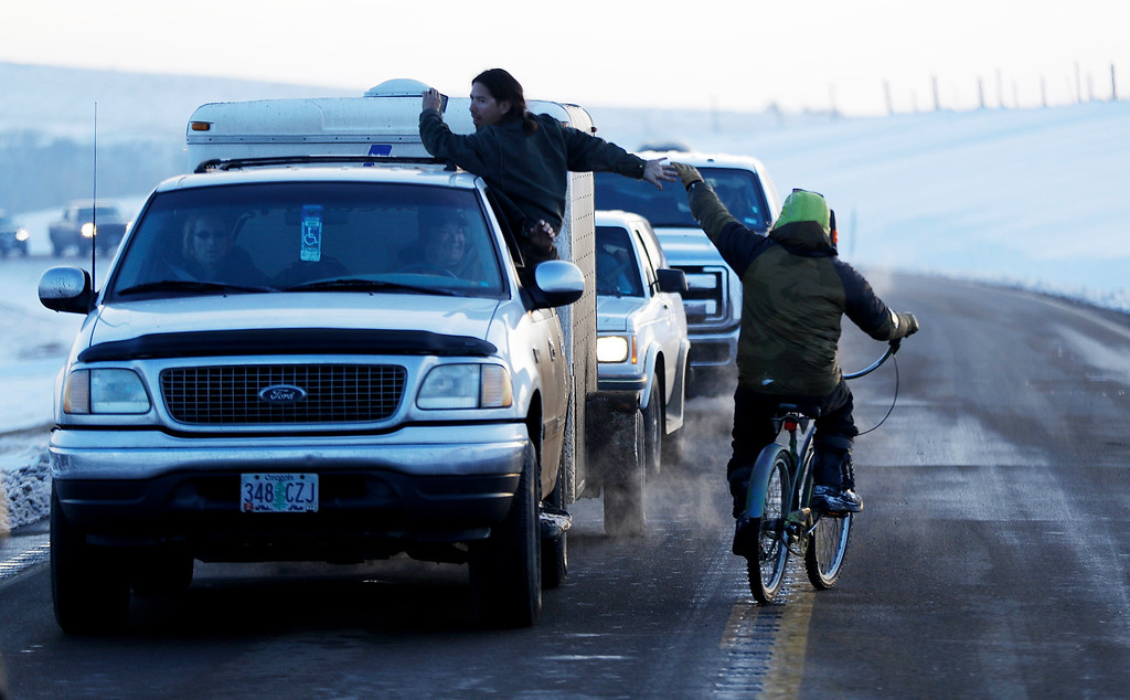 . A bicyclist and a passenger high-five one another as a line of the cars wait to enter the Oceti Sakowin camp where people have gathered to protest the Dakota Access oil pipeline in Cannon Ball, N.D., Saturday, Dec. 3, 2016. (AP Photo/David Goldman)