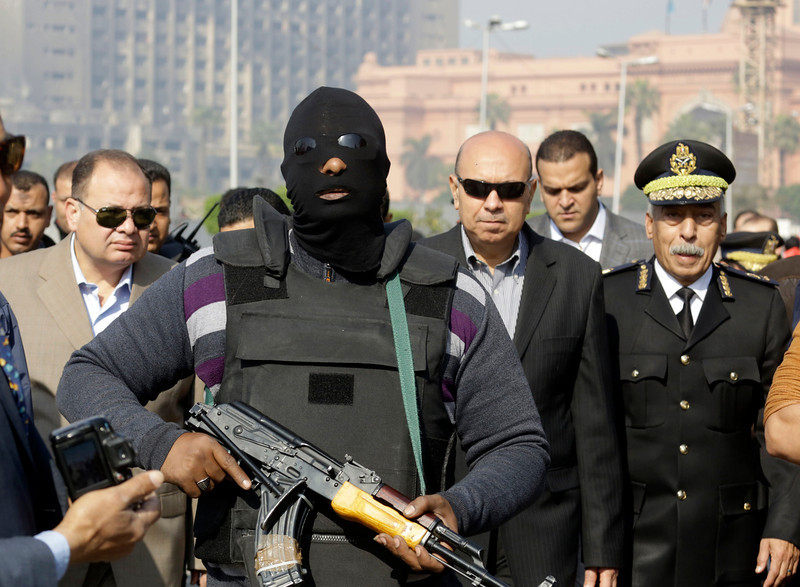 . An Egyptian masked policeman guards Cairo\'s state security chief, Osama al-Saghir, third right, as he visits Tahrir Square, the epicenter of the 2011 uprising, in Cairo, Egypt, Saturday, Jan. 25, 2014. Demonstrators began gathering Saturday in Egypt�s Tahrir Square to mark the third anniversary of the start of its 2011 revolution, though streets remained empty elsewhere in a city on edge following a spate of bombings claimed by militants. The interim government has blamed the Muslim Brotherhood group for the violence and designated it as a terrorist organization while the group denied any links to terrorism. (AP Photo/Amr Nabil)